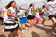 """30 JULY 2011 - PHOENIX, AZ:   Girls dance in a flash mob in downtown Phoenix, AZ, Saturday. About 200 people showed up at Heritage Square in downtown Phoenix Saturday morning for a flash mob coordinated by the Arizona Science Center. The mob danced to several hip-hop songs before disbanding. The event was a part of National Dance Day Activities and the First Lady's """"Let's Move!"""" physical fitness campaign.      PHOTO BY JACK KURTZ"""