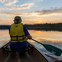A man in the bow of a canoe on Long Pond near the Appalachian Mountain Club's Gorman Chairback Lodge. Maine's 100 Mile Wilderness.