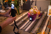 New York, NY, October 31, 2013. A man placed a mobile phone showing a photograph of a boy on the altar, and took a photo of it in front of an ofrenda, or offering, of bread and fruit.