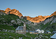 """At Meglisalp, Altmann peak (2435m) rises dramatically above a 1904 mountain chapel (Kapelle Maria zum Schnee, """"Holy Mother Mary of the Snow""""). Berggasthaus Meglisalp can only be reached on foot in the heart of the Alpstein mountain chain in the Appenzell Alps, Switzerland, Europe. This authentic mountain hostelry, owned by the same family for five generations, dates from 1897. Meglisalp is a working family dairy farm."""