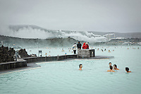 People enjoying the Blue Lagoon geothermal spa located in a lava field in Grindavík, Iceland.