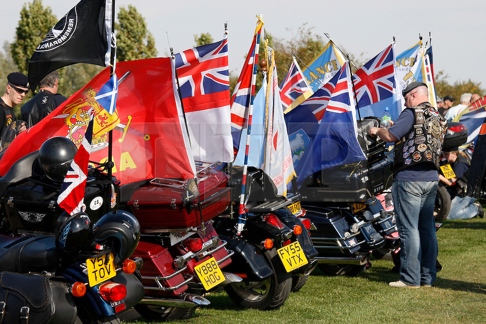 © Licensed to London News Pictures. 01/10/2011, Staafordshire, UK. The fourth annual Ride to the Wall took place today (Saturday). Thousands of motorcyclists from all over the country either as individuals or in groups rode to the National Memorial Arboretum to honour and show their support for the Armed Forces. Since the first ride in 2008 the ride has raised nearly £100,000 for the NMA. .Pictured, A biker adjusts one of the flags attached to the bikes on display at the NMA..Photo credit : Dave Warren/LNP