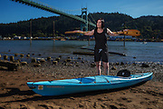 USA, Oregon, Portland, Cathedral Park, young woman with her kayak at Cathedral Park by the St. John's Bridge. MR