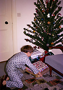 Young boy opening his presents from under the tree on Christmas morning, UK 1969