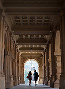 European caucasian couple walking through an archway; Prague, Czech Republic.