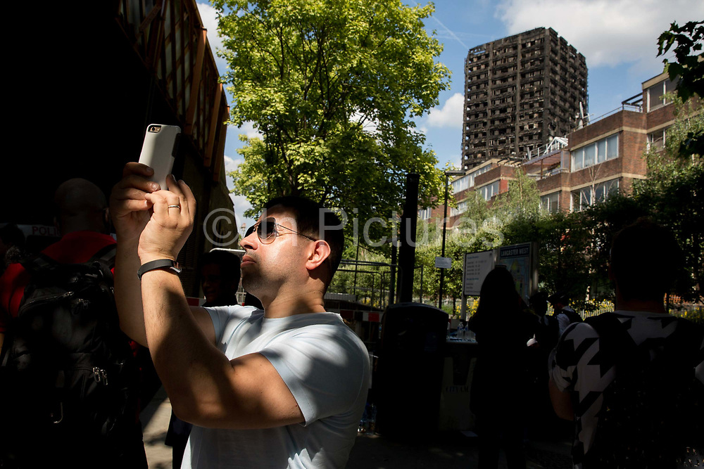A man takes a selfie of the burnt out shell of Grenfell Tower on the 17th June 2017 in North Kensington, London, United Kingdom. The Grenfell Tower fire occurred on 14th June 2017 at the 24-storey block of public housing flats in North Kensington, West London. It caused at least 80 deaths and over 70 injuries, yet the actual numbers have yet to be confirmed