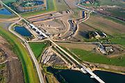 Nederland, Noord-Brabant, Werkendam, 28-10-2014; Ruimte voor de Rivier project Ontpoldering Noordwaard. Boven in beeld Fort Steurgat, omgven door nieuwe dijk (primaire waterkering). De bandijk is reeds voorzien van een doorlaat annex brug, rechts nieuwe terp voor (historische) boerderij.<br /> De Noordwaard wordt ontpolderd door de dijken aan de rivierzijde gedeeltelijk af te graven, hierdoor kan de Nieuwe Merwede bij hoogwater via de Noordwaard sneller naar zee stromen. Gevolg van de ingrepen is ook dat de waterstand verder stroomopwaarts zal dalen.<br /> National Project Ruimte voor de Rivier (Room for the River) By lowering and / or moving the dike of the Noordwaard polder the area will become subject to controlled inundation and function as a dedicated water detention district. Houses and farmhouses will be constructed on new dwelling mounds. <br /> luchtfoto (toeslag op standard tarieven);<br /> aerial photo (additional fee required);<br /> copyright foto/photo Siebe Swart