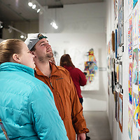 Hozho Academy teachers Elise Staffke, 24, and Ethan Williams, 22, admire their students art work at ART123 Saturday night in downtown Gallup for the opening of the 5th Annual Youth Art Show.