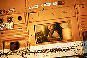 A child looks out through back window of a bus. Many children are recruited from their communities to work with low salaries in agricultural fields of Culiacan, Mexico.