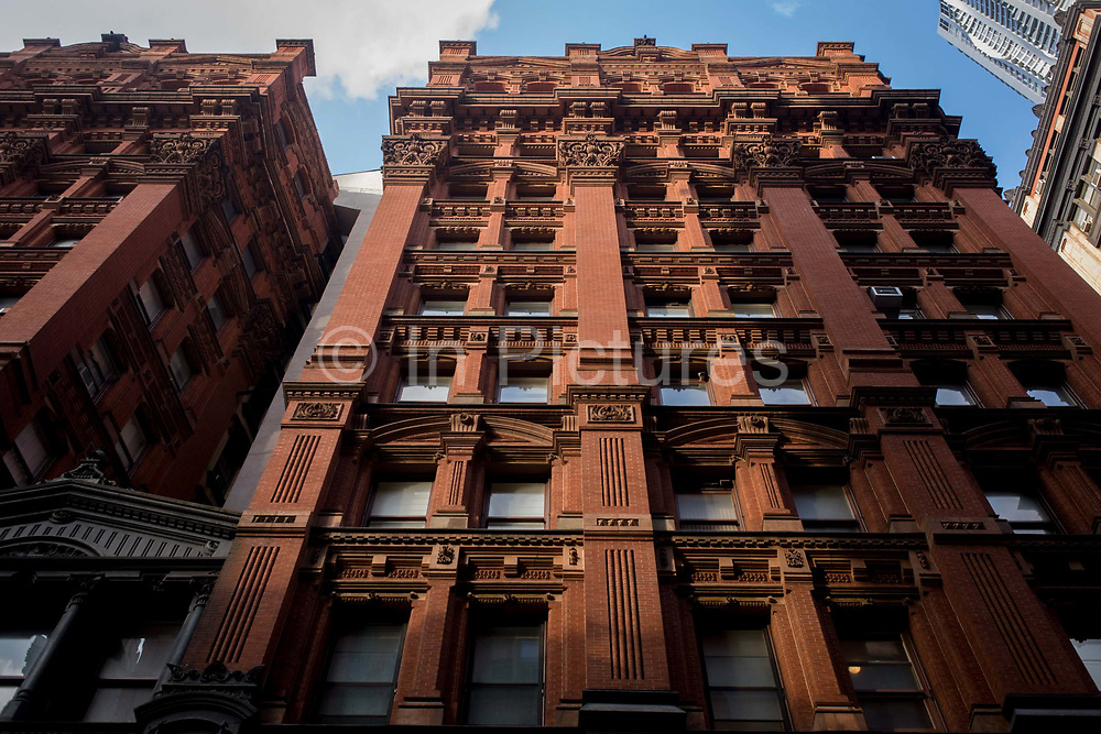Red brick apartment building in Manhattan, New York City. Looking from a low angle, we see the building rising up into the sky, a high-rise used for domestic purposes near Broadway.