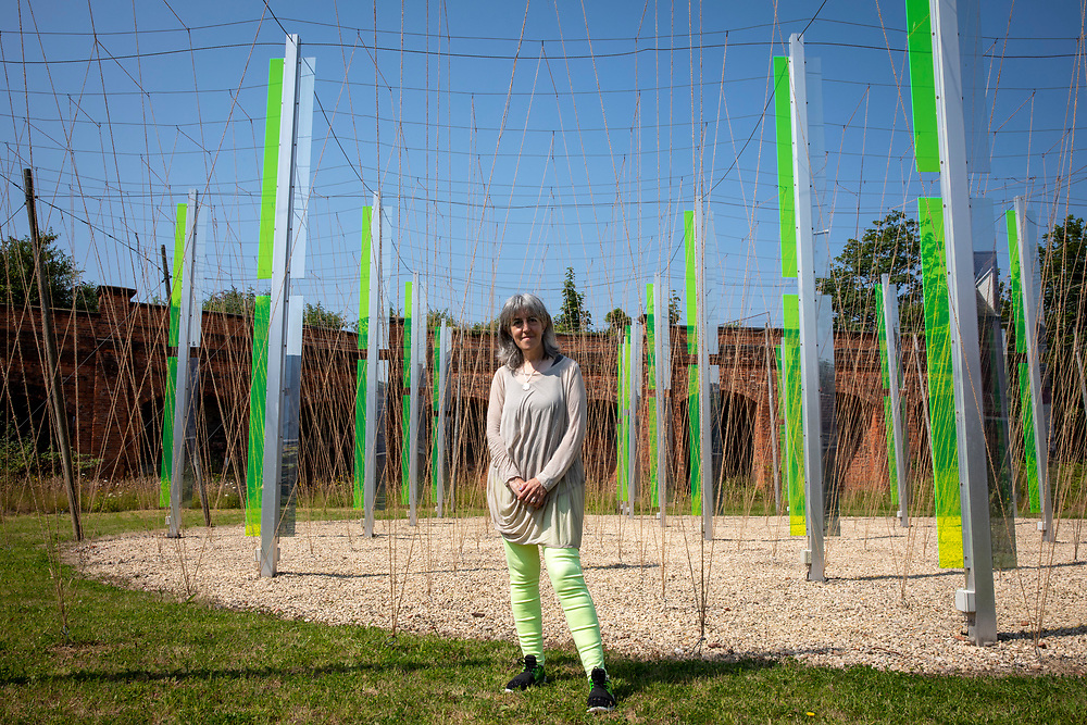Artist Jyll Bradley with her installation Green/Light part of the Folkestone Triennial launch on 20th of July 2021, in Folkestone, United Kingdom. For Folkestone Triennial 2014, Bradley presentedGreen/Light (for M.R.), a major sculptural light installation created for the former gasworks site on the junction of Ship Street and Foord Road North, Folkestone. Now derelict, the site was once a hub of energy and the place where light was first generated for the town. The creation of the installation was an intense personal journey for Bradley, who was born in Folkestone in the same year that the gasworks were decommissioned, but has lived her adult life as a successful artist in London.Since its creation, Green/Light (For M.R.) has become a highly acclaimed work and much-loved local beacon. Its reflective, exciting presence acts as a powerful catalyst for conversations on the future of the gasworks. The artwork is part of the Creative Folkestone Triennial 2020, The Plot, which sees 27 newly commissioned artworks appearing around the south coast seaside town. The new work builds on the work from previous triennials making Folkestone the biggest urban outdoor contemporary art exhibition in the UK. (photo by Andrew Aitchison / In pictures via Getty Images)