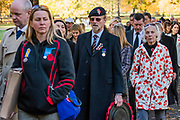 People arrive in Green Park to join the Peoples Procession also known as the Nation's Thank You Procession. They wear there own or relatives medals and many carry wreaths - Remembrance Sunday and Armistice Day commemorations fall on the same day, remembering the fallen of all conflicts but particularly the centenary of the end of World War One.