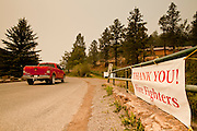 "05 JUNE 2011 - GREER, AZ:  A truck drives into Greer past a sign thanking firefighters Sunday. The fire grew to more than 180,000 acres by Sunday with zero containment. A ""Type I"" incident command team has taken command of the fire.    PHOTO BY JACK KURTZ"