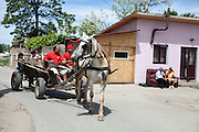 Local inhabitants with a horse-drawn carriage in the streets of the Roma area of Frumusani. In the back the local grocery store with couch.