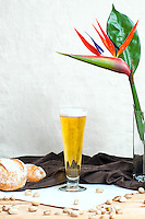 A glass of pilsner with bread and pistachios.