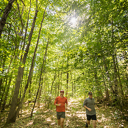 Two men trail running in a forest in Jackson, New Hampshire.