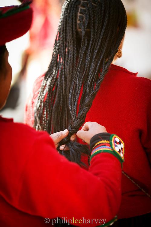 Peruvian Quechua woman wearing traditional dress, braiding hair, Chinchero Town Sunday Market, Cusco region, Peru, South America