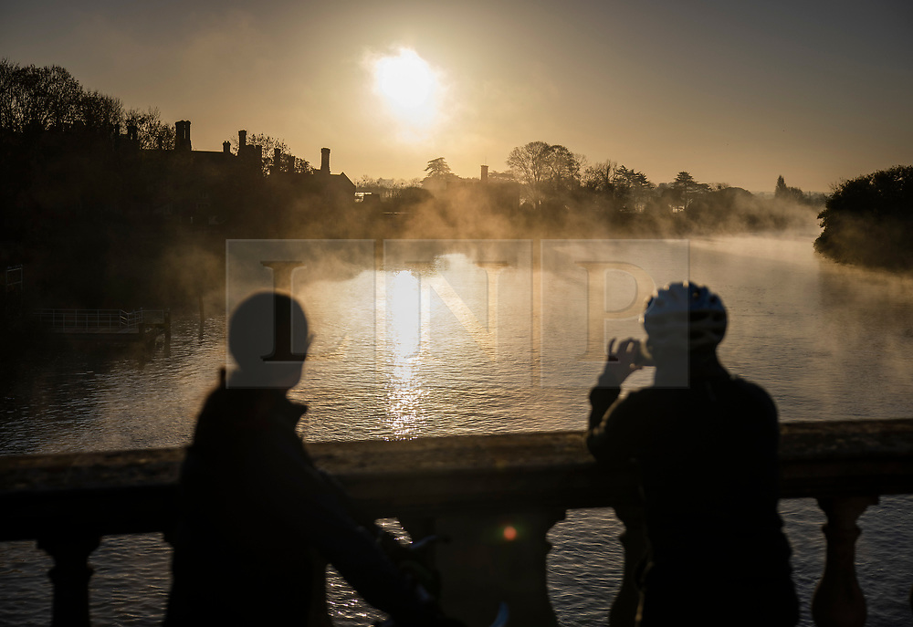 © Licensed to London News Pictures. 04/11/2020. Hampton Court, UK. Cyclists stop to look at the sunrise over a misty River Thames at Hampton Court . Low autumnal temperatures are expected in parts of the United Kingdom today. Photo credit: Peter Macdiarmid/LNP