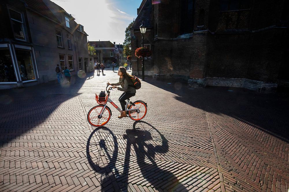 Een meisje rijdt op een Mobike door het centrum van Delft.<br /> <br /> A girl rides on a Mobike at the city center of Delft.