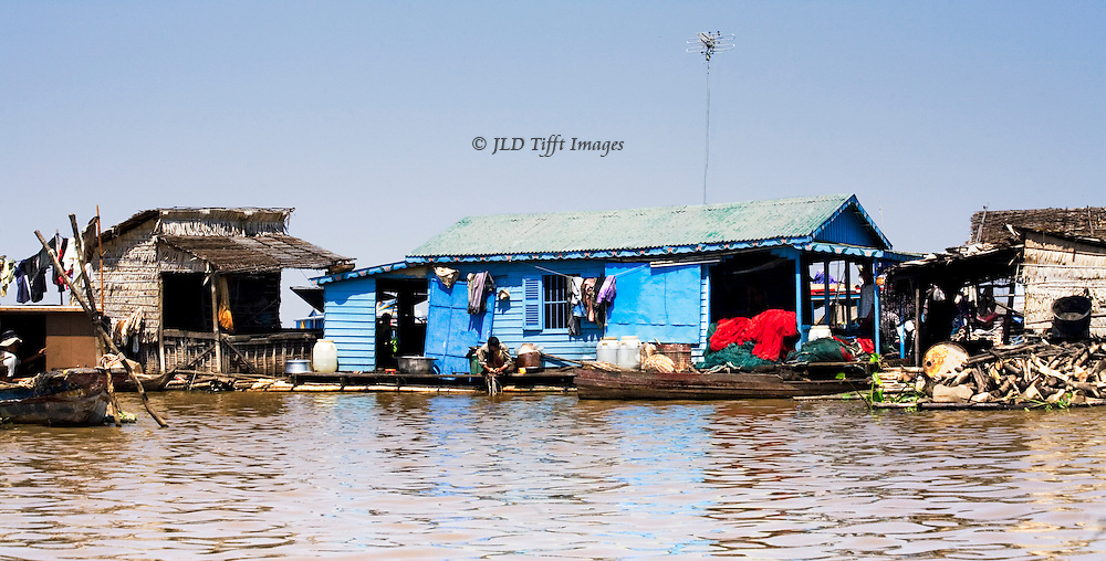 Several neighboring houses in a floating village on Tonle Sap.  One person in the center is doing laundry in the lake water.  There are other indications of daily living.