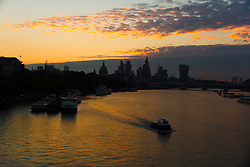 © Licensed to London News Pictures. 11/08/2017. LONDON, UK.  The sun rises behind clouds and St Paul's Cathedral and skyscrapers as a boat passes on the River Thames this morning. The capital has seen a cold start to day following a spell of wet weather this summer. Photo credit: Vickie Flores/LNP