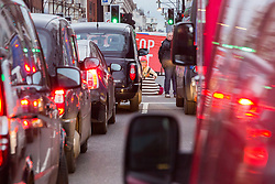 PICTURED: A protester sits on the road causing traffic to jam during rush hour. Demonstrators from the anti-pollution group Stop Killing Londoners cause traffic chaos for London commuters as they conduct a series of short roadblocks at Marble Arch stopping cars and buses from entering Oxford Street and Park Lane. Irate motorists accused them of creating more pollution than they were stopping, whilst the group said their objectives were long term. A leaflet handed out to motorists says the government is not doing enough to tackle the crisis costing 'taxpayers and the NHS £billions [sic] a year'. PLACE, January 29 2018. © Paul Davey