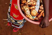 Maria Mchele carries sweet potatoes she intends to sell at Buhongwa market near Mwanza, Tanzania on Monday December 14, 2009.
