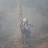 A photojournalist, in a ballistic helmet and gasmask, stands next to a lamppost to avoid being hit by teargas cannisters. Teargas works in contact with moisture, so as it goes into your nostrils, eyes or mouth is starts burning. But also as you sweat it burns. Even having a shower afterwards is painful. Several people were immobilised and screaming with it, as well as a couple of people who'd passed out, overcome by it. There have been cases of babies and elderly people being killed by it.