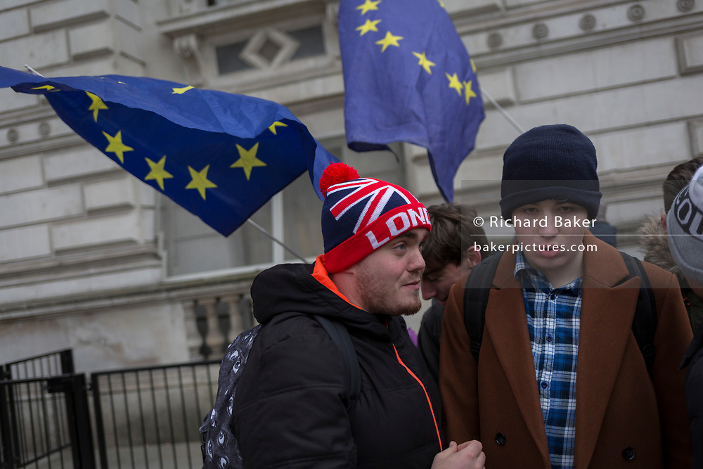 As the EU's Chief negotiator Michel Barnier meets Theresa May in London to discuss the next stage of Brexit, anti-Brexit protesters holding the stars of the EU flag in Whitehall and near Downing Street, passing a tourist wearing a London hat, the official residence of the Prime Minister, on 5th February 2018, in London England.