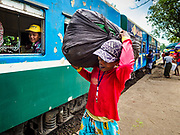 25 NOVEMBER 2017 - YANGON, MYANMAR: A passenger carrying merchandise for a Yangon market walks to the Yangon Circular Train in Danyingon station, in the middle of the train's loop. The Yangon Circular Train is a 45.9-kilometre (28.5 mi) 39-station two track loop system connects satellite towns and suburban areas to downtown. The train was built during the British colonial period, the second track was built in 1954. Trains currently run both directions (clockwise and counter-clockwise) around the city. The trains are the least expensive way to get across Yangon and they are very popular with Yangon's working class. About 100,000 people ride the train every day. A a ticket costs 200 Kyat (about .17¢ US) for the entire 28.5 mile loop.    PHOTO BY JACK KURTZ