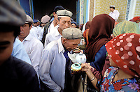 """Chine. Province du Sinkiang (Xinjiang). Kashgar (Kashi), sortie de la priere du vendredi, mosquee Id Kah // Exit of the Id Kah mosque on friday,  man's blow on the tea pot from ill family to give them """"purity"""", Kashgar, Sinkiang, China"""