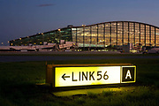 "An exterior view of Heathrow Airport's Terminal 5 building in West London. Created by the Richard Rogers Partnership (now Rogers Stirk Harbour and Partners). A lit airfield navigation taxiway sign shows the route number and code for pilots to find their way around the confusing network of taxiways and there are 1 million square metres of new apron and taxiway pavement for T5. At a cost of £4.3 billion, the 400m long T5 is the largest free-standing building in the UK with the capacity to serve around 30 million passengers a year. The Terminal 5 public inquiry was the longest in UK history, lasting four years from 1995 to 1999. From writer Alain de Botton's book project ""A Week at the Airport: A Heathrow Diary"" (2009)."