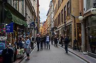 Stockholm, Sweden -- July 16, 2019. Crowds of shoppers in Old Town, Stockholm, examine goods for sale.