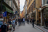 Stockholm, Sweden -- July 16, 2019. Crowds of shoppers in Old Town, Stockholm, examine goods for sale.