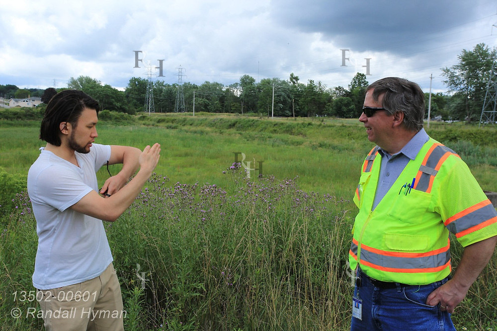 Hyfi CEO Brandon Wong talks with Michael Blair, a project manager with the Northeast Ohio Regional Sewer District, beside a large detention basin for controlling stormwater overflow in Parma, Ohio.