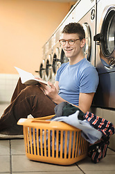 Portrait of young man waiting in laundry, smiling