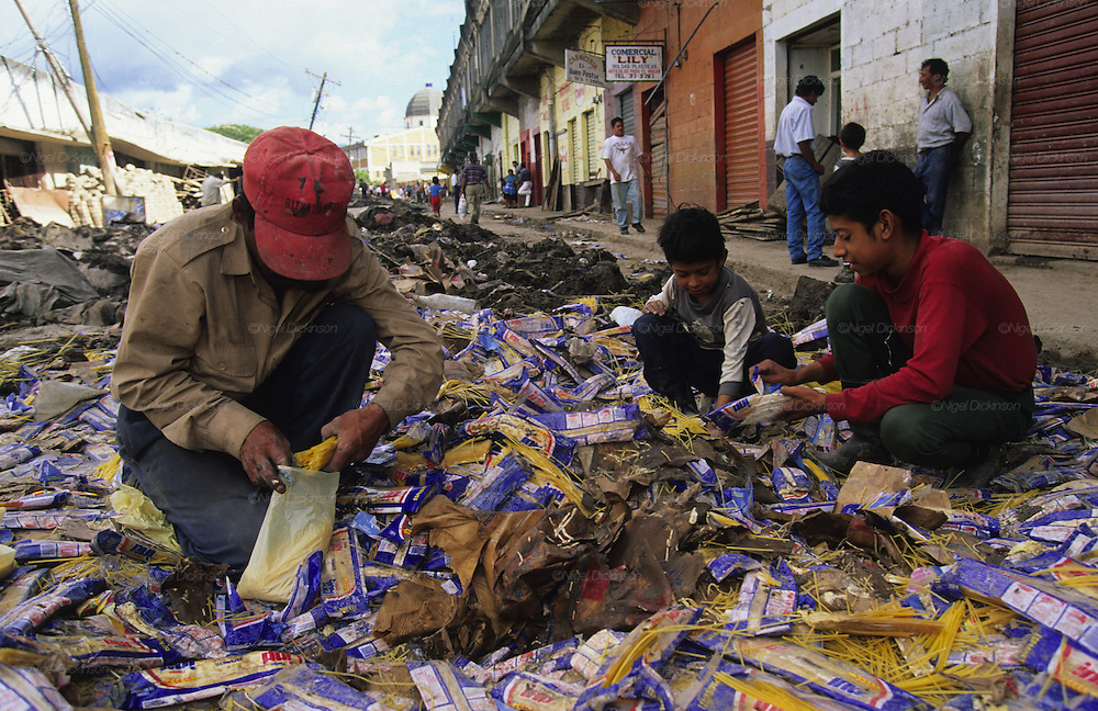 Central America, Honduras, Tegucigalpa. Hungry youths searching for food. Devastation in the aftermath of Hurricane Mitch. High winds and flooding. Children scavenging for food, collecting thrown away or destroyed spaghetti. Infrastructure destroyed.