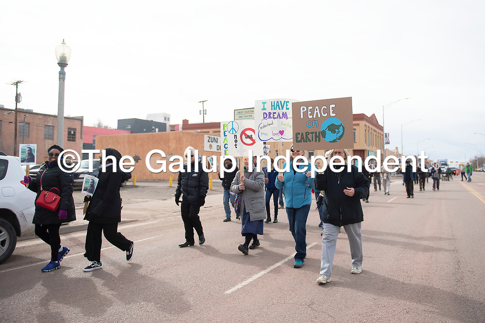 Following an interfaith gathering at the Gallup Cultural Center attendees walk Route 66 in downtown Gallup to the Larry Brian Mitchell Recreation Center for a tribute to Martin Luther King, Jr. Monday afternoon.