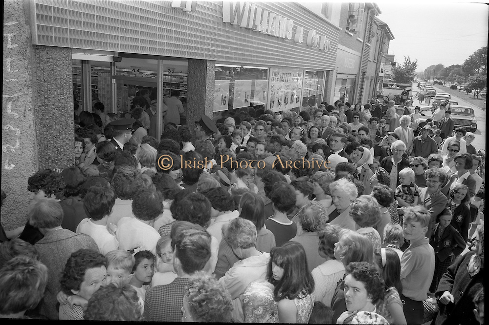 29/06/1965<br /> 06/29/1965<br /> 29 June 1965<br /> Opening of new H. Williams and Co. Ltd. Supermarket at Deansgrange, Dublin. Image shows a part of the crowd that gathered for the opening of the new shop. Note Garda presence at the door for crowd control!