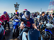 22 JANUARY 2019 - PHRA PRADAENG, SAMUT PRAKAN, THAILAND: Passengers on a motorcycle and vehicle ferry going across the Chao Phraya River in Phra Pradaeng, in the suburbs south of Bangkok. The use of vehicle ferries across the river has gone down as the government has built bridges to connect communities on both sides of the river. The Phra Pradaeng ferries are the busiest ferries in the Bangkok metropolitan area. Since the BTS Skytrain now stops a few kilometers from the ferry, the number of commuters going into Bangkok that use the ferry has increased.      PHOTO BY JACK KURTZ