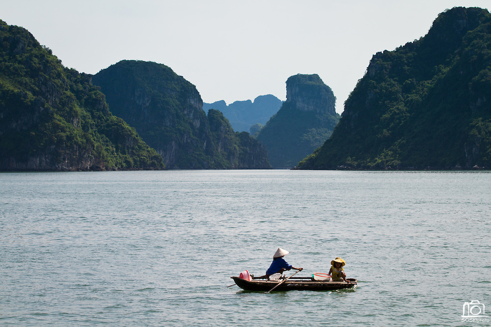 A woman and her child row a small boat through Halong Bay, Vietnam.  Fishermen have developed floating viallages which contain banks and other commercial stores along the caves of Halong Bay.  Photo by Stan Olszewski/SOSKIphoto