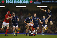 Stuart McInally of Scotland © looks to offload the ball to Byron McGuigan of Scotland (r jumping)  as Rhys Patchell of Wales tackles in the 1st half. Wales v Scotland, NatWest 6 nations 2018 championship match at the Principality Stadium in Cardiff , South Wales on Saturday 3rd February 2018.<br /> pic by Andrew Orchard, Andrew Orchard sports photography