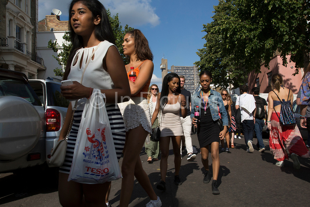 Group of friends walk along Golborne Road with Trellick Tower in the distance on Monday 28th August 2016 at the 50th Notting Hill Carnival in West London. A celebration of West Indian / Caribbean culture and Europes largest street party, festival and parade. Revellers come in their hundreds of thousands to have fun, dance, drink and let go in the brilliant atmosphere. It is led by members of the West Indian / Caribbean community, particularly the Trinidadian and Tobagonian British population, many of whom have lived in the area since the 1950s. The carnival has attracted up to 2 million people in the past and centres around a parade of floats, dancers and sound systems.