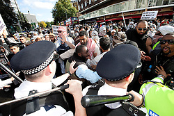 © Licensed to London News Pictures. 11/09/2011. London, UK. Police scuffle with Muslims Against Crusaders protesters as they are lead to Regents Park Mosque following their protest. Radical Islamist group, Muslims Against Crusades, hold a protest outside the US Embassy in Grosvenor Square, London, on the 10th anniversary of the September 11th terrorist attacks on America. A counter-protest was held at the same time by the English Defence League. Photo credit : Joel Goodman/LNP