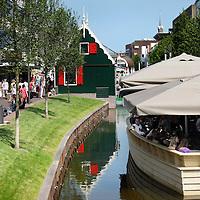 Nederland, Zaandam , 6 juli 2013.<br /> Wandeling door de binnenstad van Zaandam.<br /> Starten bij De Werf aan de Oostzijde. Daarvandaan kun je lopen op een soort boulevard tussen de flats en het water. De eerste stop is De Fabriek, filmhuis en eetcafé met terras aan de Zaan met uitzicht op de sluis. Daarna de sluis zelf.<br /> Dan langs het winkelgebied richting de Koekfabriek: Het oude Verkade pand dat is verbouwd en waar nu de bieb en sportschool en restaurant etc. in zitten.<br /> (Dat is aan de overkant van het startpunt) en misschien nog de Zwaardemaker meepakken aan de Oostzijde. Dat is een oud pakhuis die Rochdale enige jaren geleden heeft verbouwt tot appartementen met een stukje Nieuwbouw.<br /> Ook doen: het Russische buurtje vlakbij de Zaan. Dit jaar staat Rusland in de schijnwerpers en Zaandam heeft een speciale band met Rusland, vanwege het Czaar Peterhuisje en de Russische buurt. <br /> Op de foto: Winkelend publiek en drinkend publiek aan de gedempte gracht.<br /> Foto:Jean-Pierre Jans
