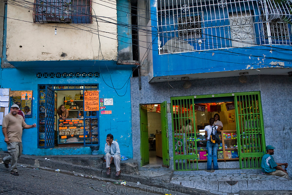 """Katherine Navas, a high school student  (behind counter in shop on right), tends to a customer behind the counter of her stepfather's Internet and copy shop in Caracus, Venezuela. (From the book What I Eat: Around the World in 80 Diets.)  Bars on all the windows, doors, and balconies signal that security is a major concern in this neighborhood. Caracas was the murder capital of the world in 2008; 50 murders in one weekend is not unheard of. Local gangs are viciously territorial and ruthless in their victimization of the hardworking, law-abiding majority. Noemi Hurtado, an 83-year-old who has lived a stone's throw from Katherine's house for the past 51 years, has never once crossed into the barrio of La Silsa. """"It's too dangerous,"""" she says. """"I would never go there."""" When Noemi moved to western Caracas, the La Silsa barrio didn't yet exist; the hills surrounding the valley were forested and, she remembers, there were waterfalls."""