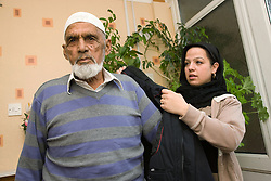 Young woman helping older man to put on his coat,