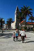 Two adults and two children (5 years old, 9 years old) walking toward church and tower of the Sveti Duje (Saint Dominic) Monastery. Trogir, Croatia