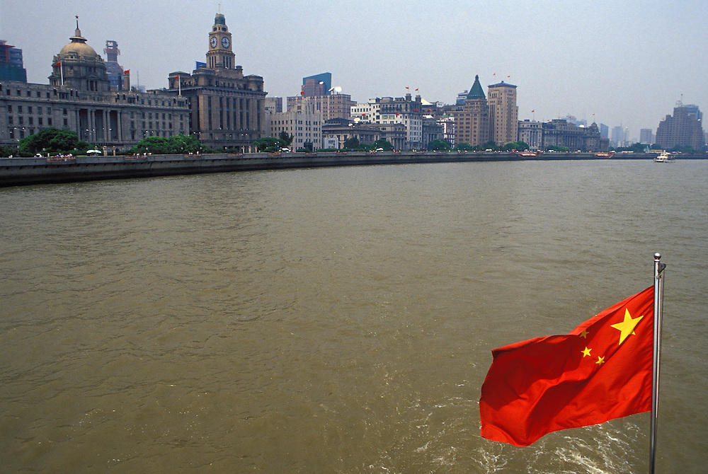 Julio 2005. La bandera china ondea en un barco que navega por el río Huangpu a su paso por el Bund en Shanghai.