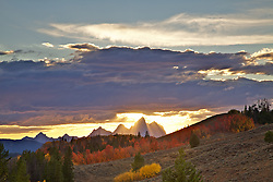 """The light beams of sunset stream through the Grand Tetons and illuminate the fall colors of red and golden aspen of Jackson Hole wyoming, Crepuscular Rays<br /> <br /> For production prints or stock photos click the Purchase Print/License Photo Button in upper Right; for Fine Art """"Custom Prints"""" contact Daryl - 208-709-3250 or dh@greater-yellowstone.com"""